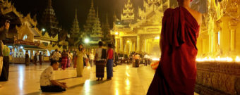 A Buddhist monk in reflection at Shwedagon Pagoda in Myanmar.