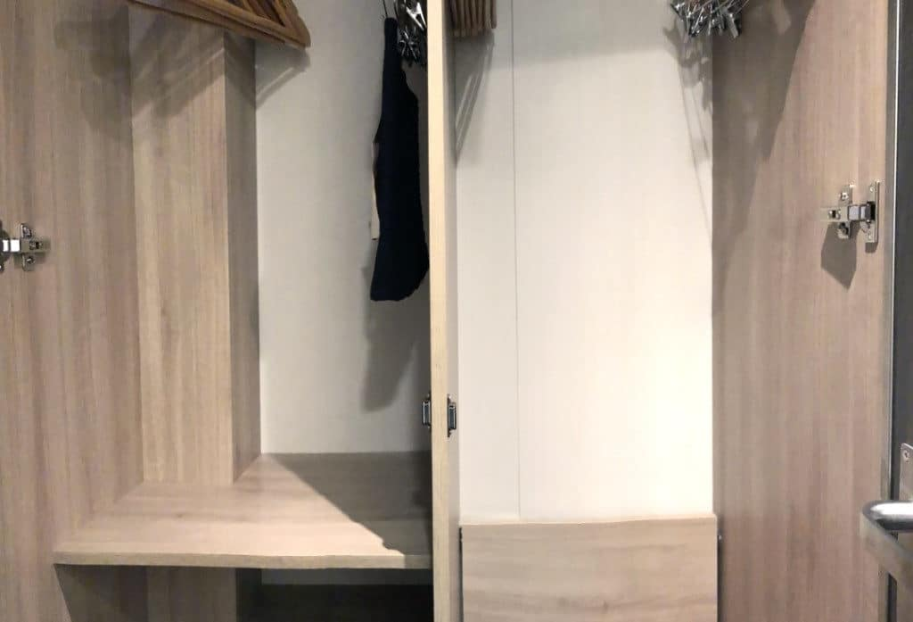 The closet has plenty of hanging space as well as adjustable shelving.
